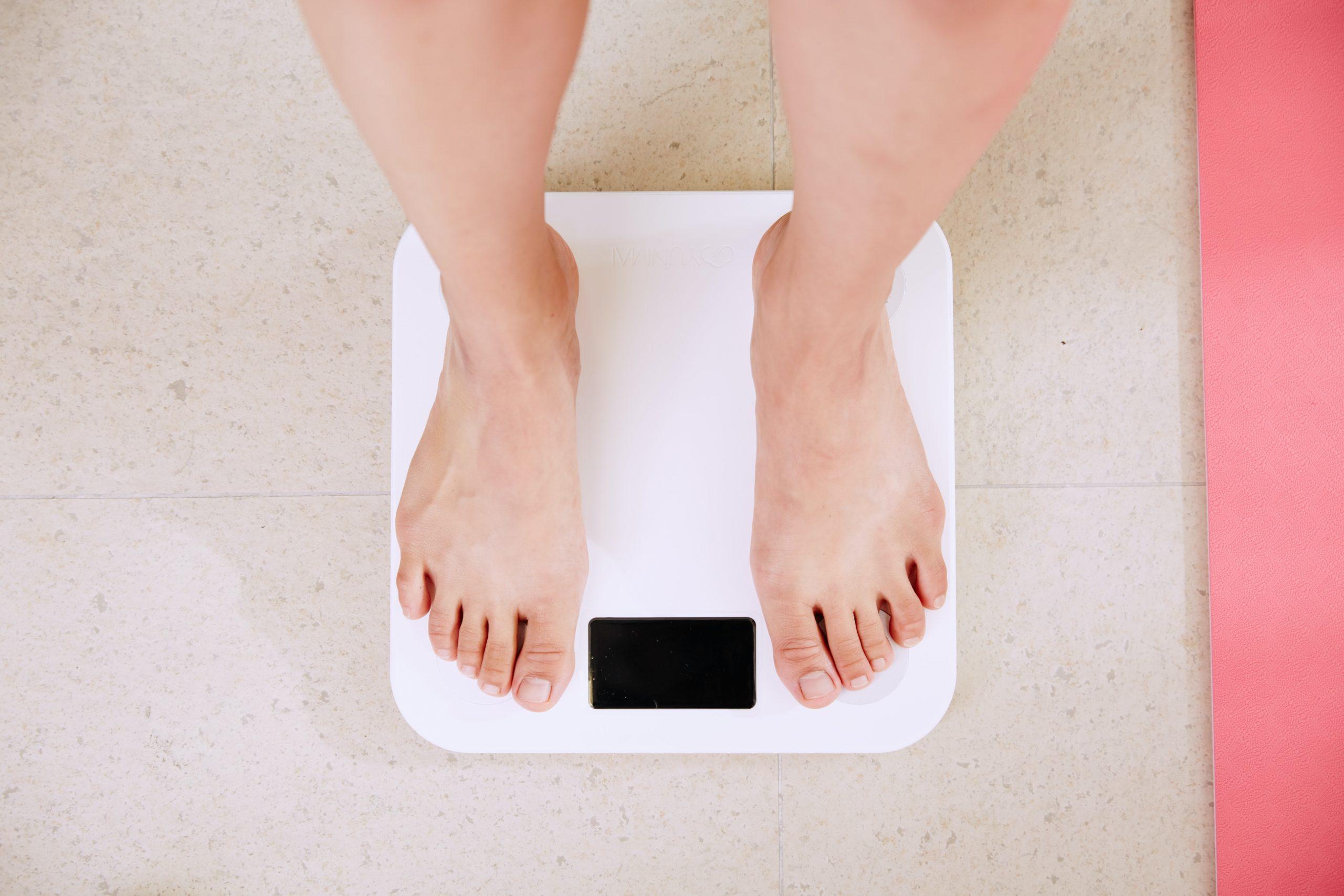 体重計で測る人の画像